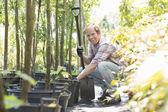 Gardener crouching while holding shovel — Stok fotoğraf