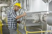 Worker turning large valve — Stockfoto