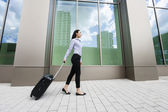 Businesswoman walking with luggage — Stock Photo