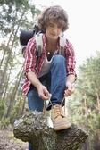 Male backpacker tying shoelace — Stock Photo