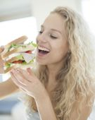 Woman eating large sandwich — Stock Photo