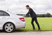 Businessman pushing broken down car — Stock Photo
