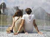 Couple sitting on fountain wall — Stock Photo