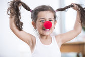 Girl wearing clown nose — Stock Photo