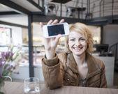 Woman displaying cell phone — Stok fotoğraf