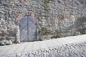 Ancient door by cobblestone street — Stock Photo