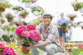 Happy gardener holding flower pot — Stock Photo
