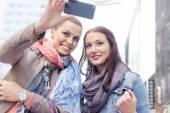 Women in jackets taking self portrait — Stockfoto