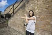 Woman exercising against brick wall — Stock Photo