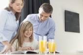 Parents assisting daughter in homework — Stock Photo