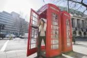 Woman opening door of telephone booth — Photo