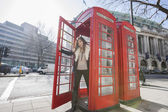 Woman opening door of telephone booth — Stock Photo
