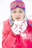 Woman wearing winter coat blowing snow outdoors — Stock Photo