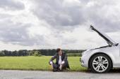 Young businessman sitting by broken down car — Stock Photo