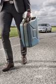 Businessman carrying gas can — Stock Photo