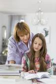 Mother guiding daughter in doing homework — Stock Photo
