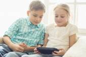 Siblings playing hand-held video game — Stock Photo