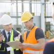Workers discussing over clipboard — Stock Photo #57281531