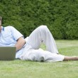 Man using laptop while lying on grass — Stock Photo #57282443