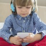 Cute boy listening to music — Stock Photo #57287105