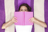 Woman covering face with book — Stock Photo