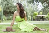 Woman in sundress sitting at park — Stockfoto