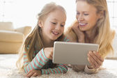 Mother and daughter using digital tablet — Stock Photo