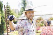 Smiling gardener carrying rake on shoulders — Stock Photo