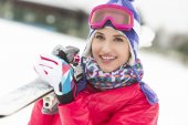 Woman carrying skis in snow — Stock Photo