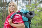 Female backpacker in raincoat looking away — Stock Photo
