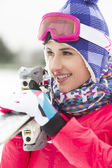 Young woman carrying skis — Stock Photo