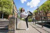 Woman exercising on sidewalk — Stock Photo