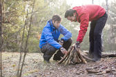 Hikers arranging firewood — Stock Photo