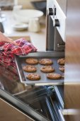 Hand removing cookie tray from oven — Stock Photo