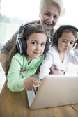 Woman with granddaughters listening to music — Stock Photo