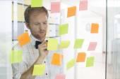 Businessman writing on sticky paper — Stock Photo