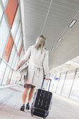 Businesswoman with luggage walking — Stock Photo