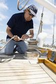 Man winching rope on yacht — Zdjęcie stockowe
