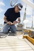 Man winching rope on yacht — Stockfoto