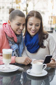 Women using cell phone — Stock Photo