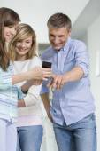 Father and daughters using smart phone — Stock Photo