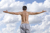 Man standing arms outstretched — Stock Photo