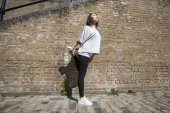 Woman stretching against brick wall — Stock Photo