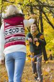 Couple playing with autumn leaves — Stock Photo