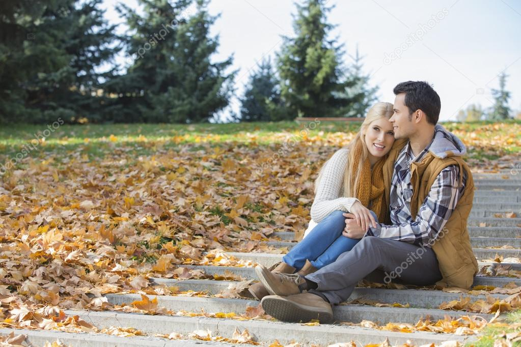 Couple hugging while sitting on steps   Stock Image. Couple hugging while sitting on steps   Stock Photo