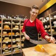 Salesperson cutting cheese i — Stock Photo #57361375