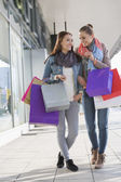 Friends communicating while carrying shopping bags — Stock Photo