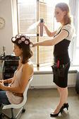Female hairdresser spraying hairspray — Stock Photo