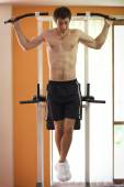 Man hanging on pull up bar — Stock Photo