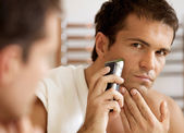 Man shaving with electric shaver — Stock Photo